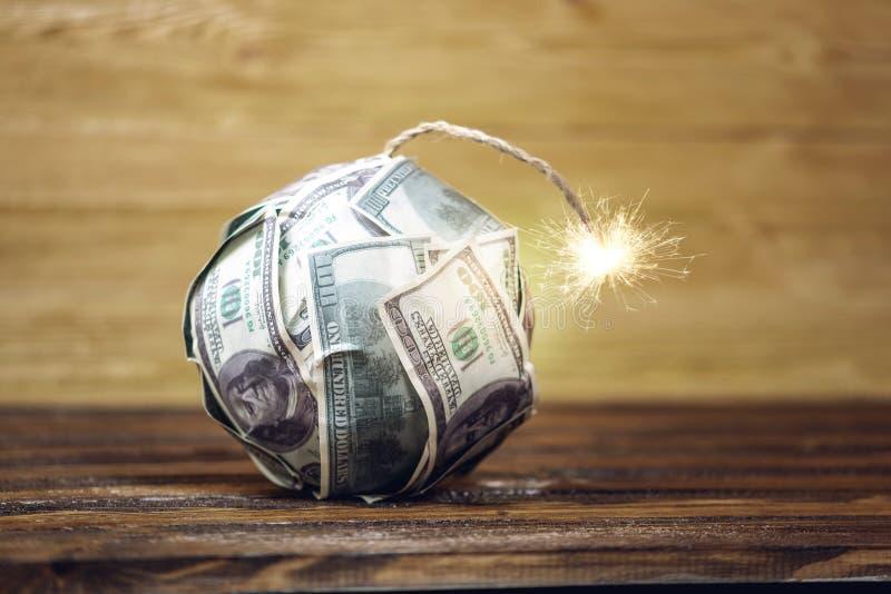 Bombardera av pengar, hundra-dollar r?kningar med en brinnande s?kring Explosion av investeringmarknader fallande finansiell hast royaltyfri bild