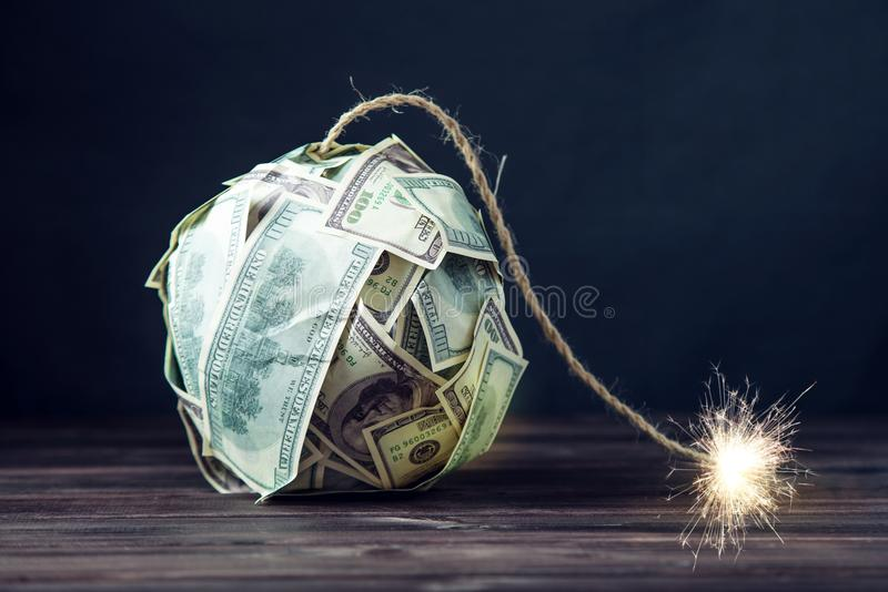 Bombardera av pengar hundra dollarräkningar med en brinnande filt Liten tid för explosionen finansiell begreppskris royaltyfri foto