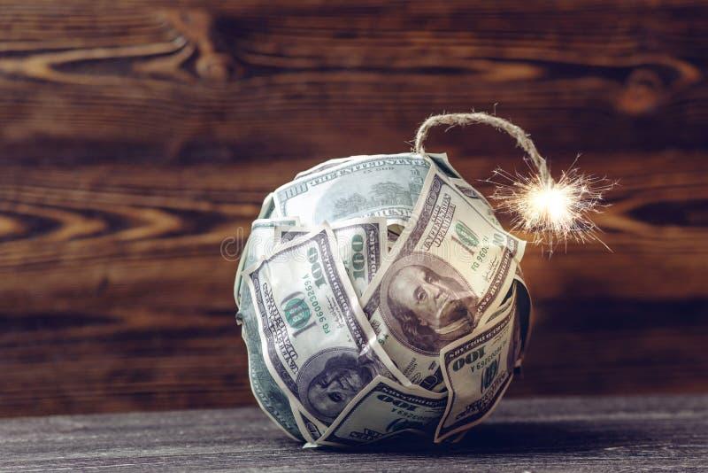 Bombardera av pengar som dynamit, hundra-dollar räkningar med en brinnande säkring Begrepp av finanskriets royaltyfria foton