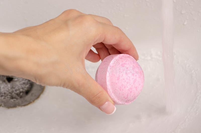 Bombardera för bad i händerna av badrumvattnet arkivfoto
