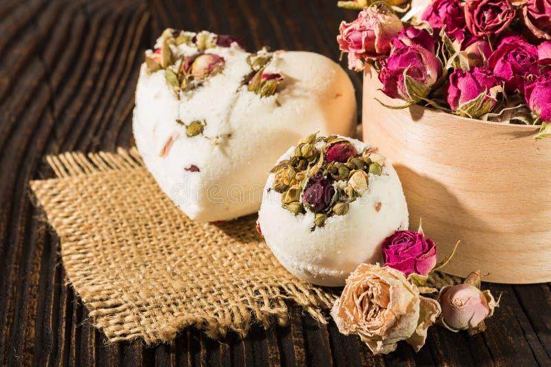 Bombardez le bain de sel décoré des roses sèches sur un fond en bois images stock