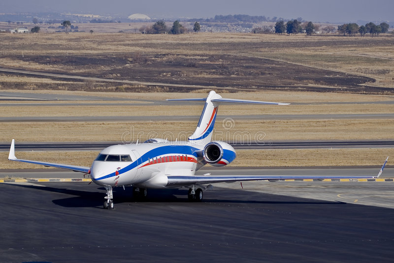 Bombardier BD-700-1A11 Global 5000. Parked on the the apron. Also visible in the background is the flat, wide open landscape. FALA — Lanseria royalty free stock photos