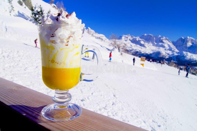 Bombardino avec la crème fouettée sur les pentes de montagne photos stock