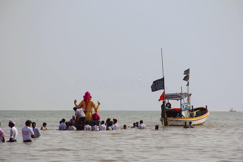 BOMBAY, MAHARASHTRA, septiembre de 2017, gente lleva el ídolo de Ganapati para la inmersión en el mar en barcos de madera en Girg imagen de archivo libre de regalías
