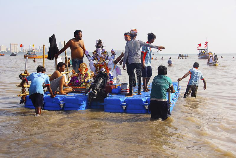 BOMBAY, MAHARASHTRA, septiembre de 2017, gente lleva el ídolo de Ganapati para la inmersión en el mar en barcos de madera en Girg fotos de archivo libres de regalías