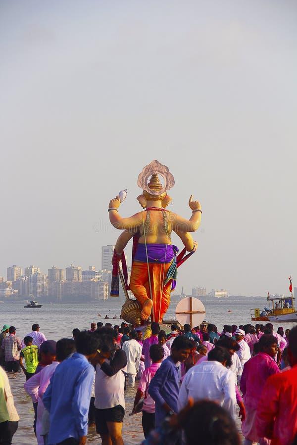 BOMBAY, MAHARASHTRA, septiembre de 2017, gente lleva el ídolo de Ganapati para la inmersión en el mar en barcos de madera en Girg imagen de archivo