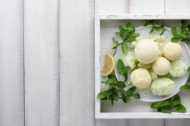 Bombe fatte a mano del bagno della menta con le erbe fresche in vassoio bianco fotografie stock