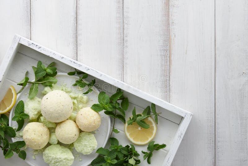 Bombe fatte a mano del bagno della menta con le erbe fresche in vassoio bianco immagini stock