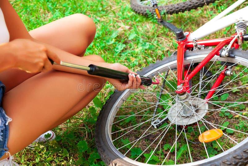 Bombeamento de m?os do ` s da mulher acima um pneu da bicicleta usando a bomba de m?o pequena fotografia de stock