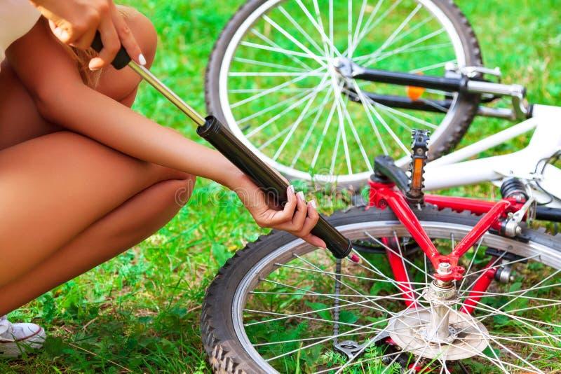 Bombeamento de m?os do ` s da mulher acima um pneu da bicicleta usando a bomba de m?o pequena imagens de stock royalty free