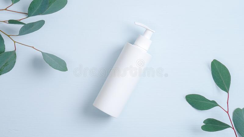 Bombear una botella de plástico para el dispensador de gel íntimo o jabón líquido sobre fondo azul con hojas de eucalipto verde H imagen de archivo