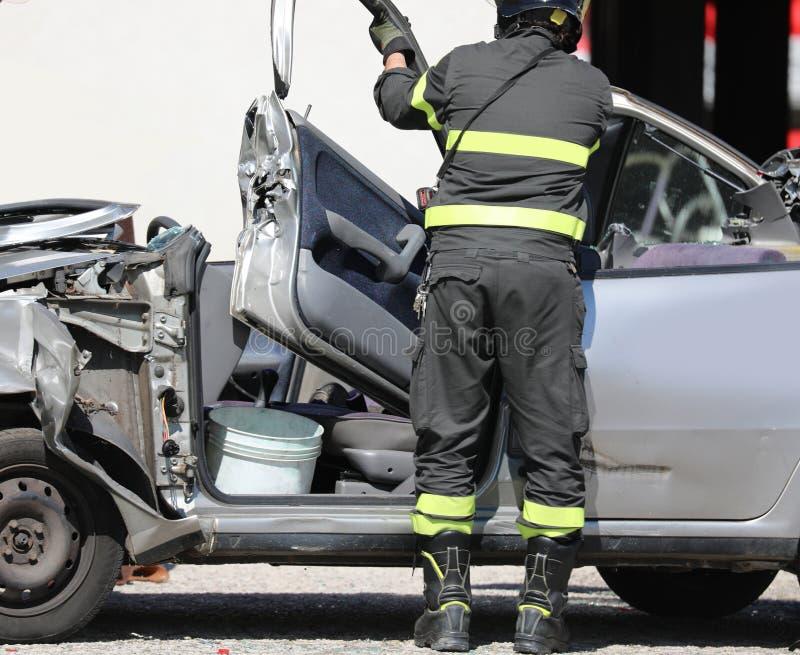 bombeiro abre o carro danificado após o acidente rodoviário foto de stock