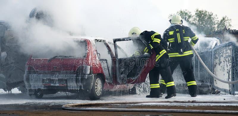 Bombeiros no incêndio do carro foto de stock royalty free