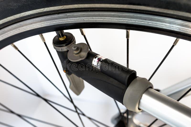 Bombeo de la rueda de bicicleta usando una bomba de mano con el indicador de presión de aire de unidades de la barra/PSI foto de archivo