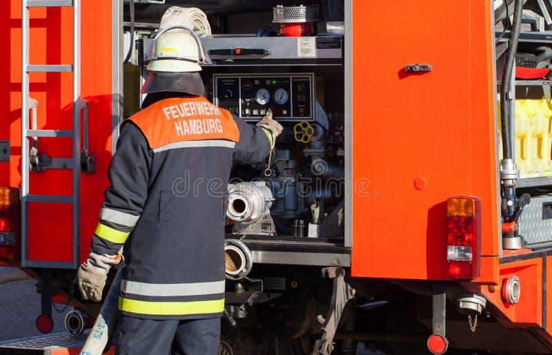 Bombero alemán del cuerpo de bomberos en el coche de bomberos imagen de archivo