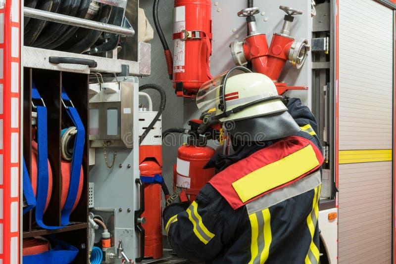 Bombero con un extintor en el coche de bomberos fotografía de archivo