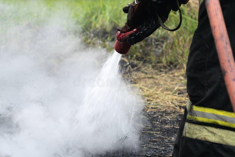 Bombero durante extintor, entrenando para superar zona de fuego del entrenamiento psicológico para los bomberos imagenes de archivo