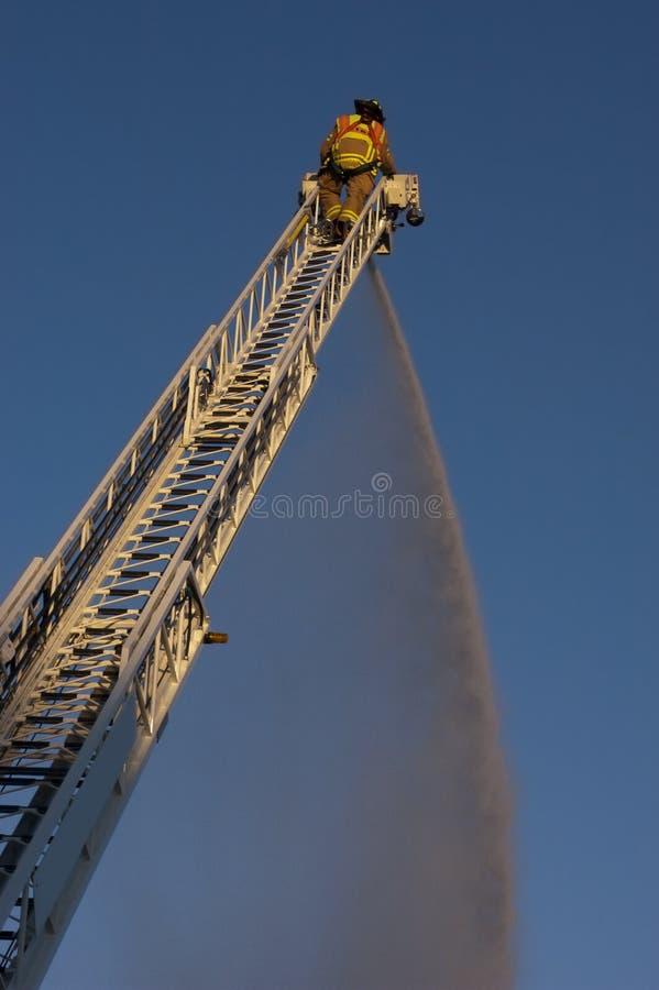 Bombero en el agua del aerosol del carro de escala en el fuego imagenes de archivo
