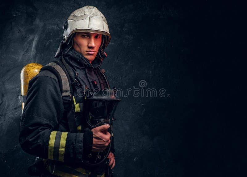 Bombero en la tenencia de equipo protector completa una máscara de oxígeno y mirada de una cámara imagen de archivo