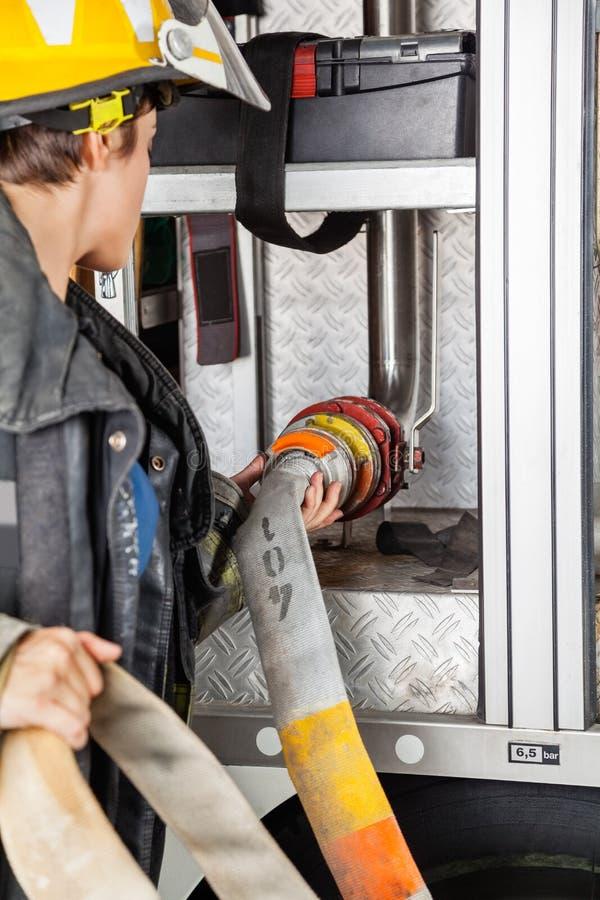 Bombero Fixing Water Hose en Firetruck fotos de archivo
