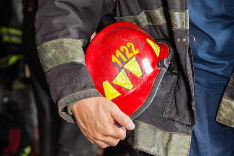 Bombero Holding Red Helmet en el parque de bomberos imagen de archivo