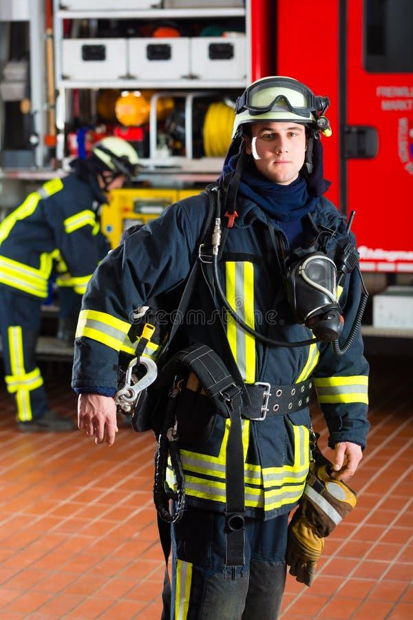 Bombero joven en uniforme delante del firetruck fotos de archivo