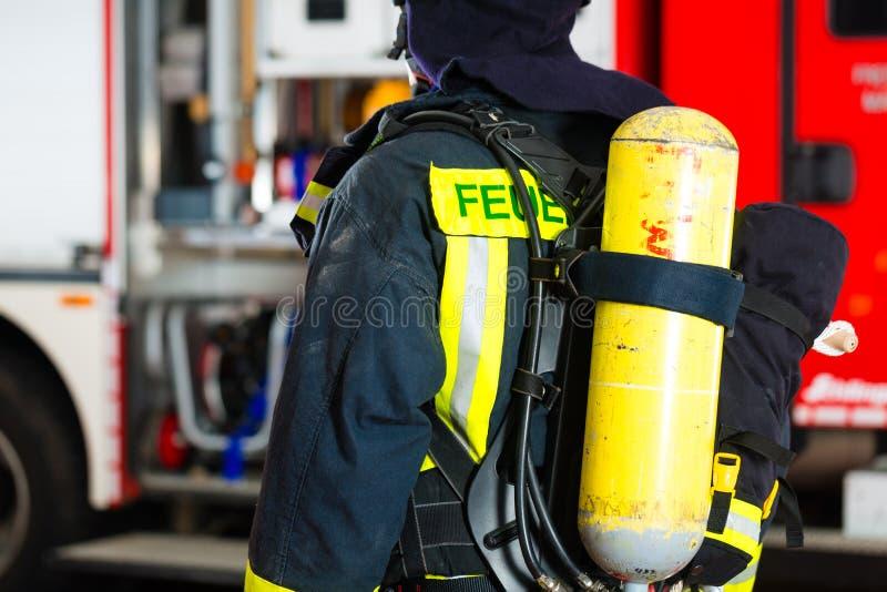 Bombero joven en uniforme delante del firetruck imagen de archivo