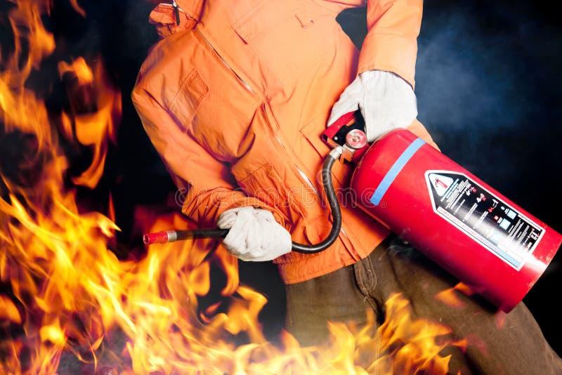 Bombero que lucha un fuego que rabia con las llamas grandes imagen de archivo libre de regalías