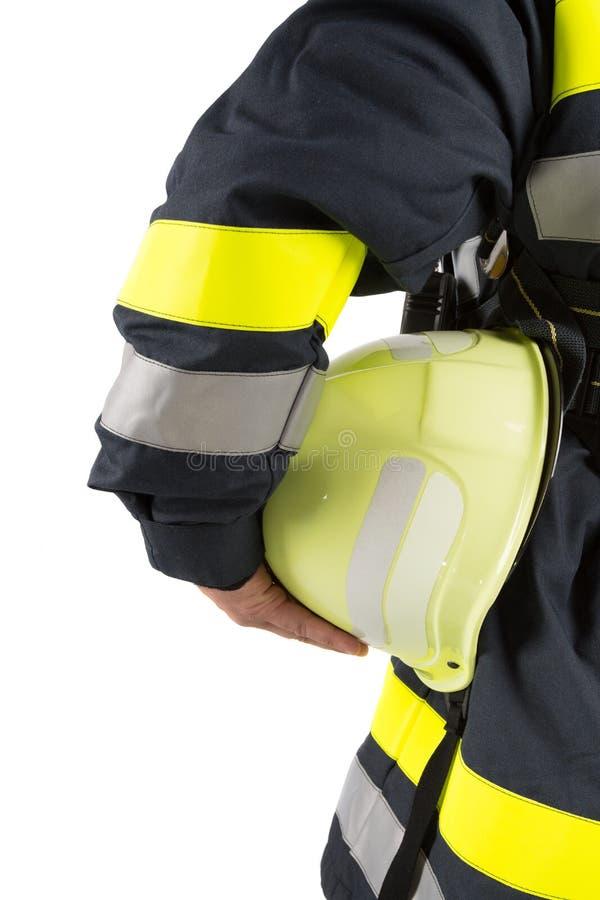 Bombero que sostiene el casco aislado en blanco foto de archivo