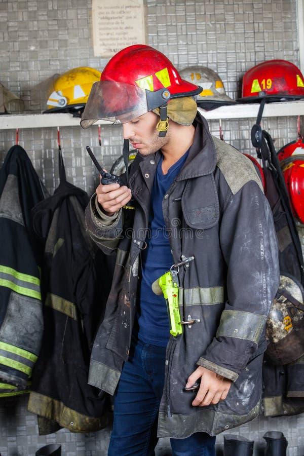 Bombero Using Walkie Talkie en el parque de bomberos fotos de archivo