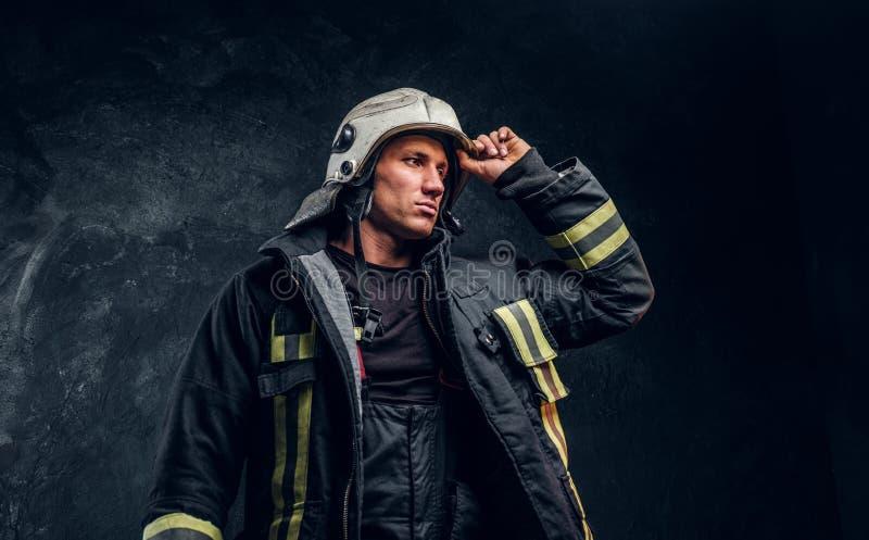 Bombero valiente en un traje del fuego que mira de lado y que corrige el casco con su mano fotos de archivo libres de regalías