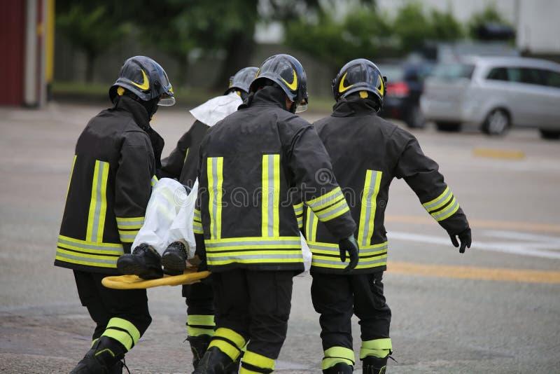 Bomberos con el ensanchador después de un accidente de carretera trágico fotografía de archivo