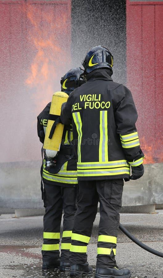 Bomberos con las botellas de oxígeno del fuego durante un entrenamiento fotos de archivo libres de regalías