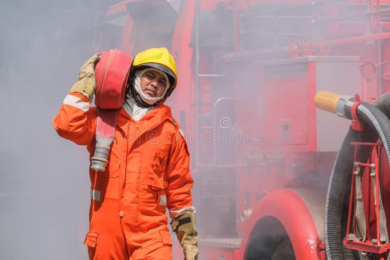Bomberos que entrenan a práctica del equipo a luchar con el fuego en la situación de emergencia Un bombero lleva una manguera del fotografía de archivo libre de regalías
