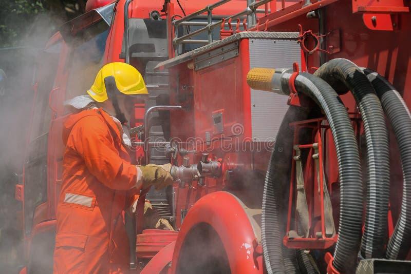 Bomberos que entrenan a práctica del equipo a luchar con el fuego en la situación de emergencia Una manguera de la fijación del b imagen de archivo
