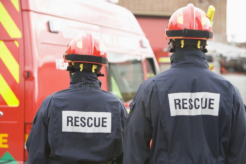 Bomberos que hacen una pausa un pequeño coche de bomberos foto de archivo libre de regalías