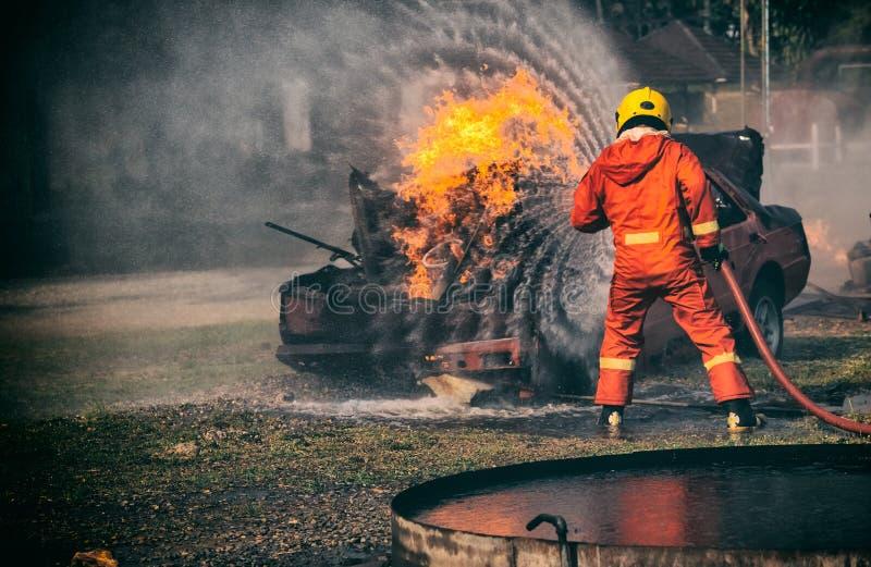Bomberos que luchan un fuego, el entrenamiento del bombero con el gas y f foto de archivo