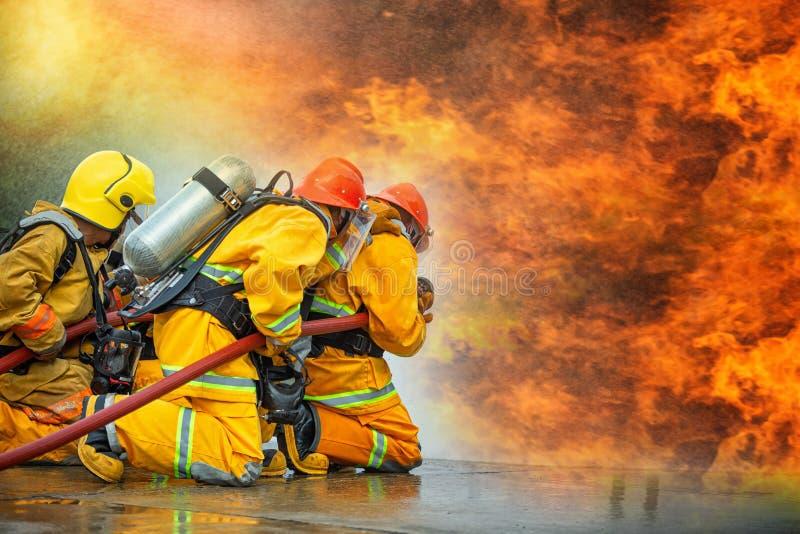 Bomberos que roc?an el agua de alta presi?n para encender con el espacio de la copia, hoguera grande en el entrenamiento, bombero fotografía de archivo