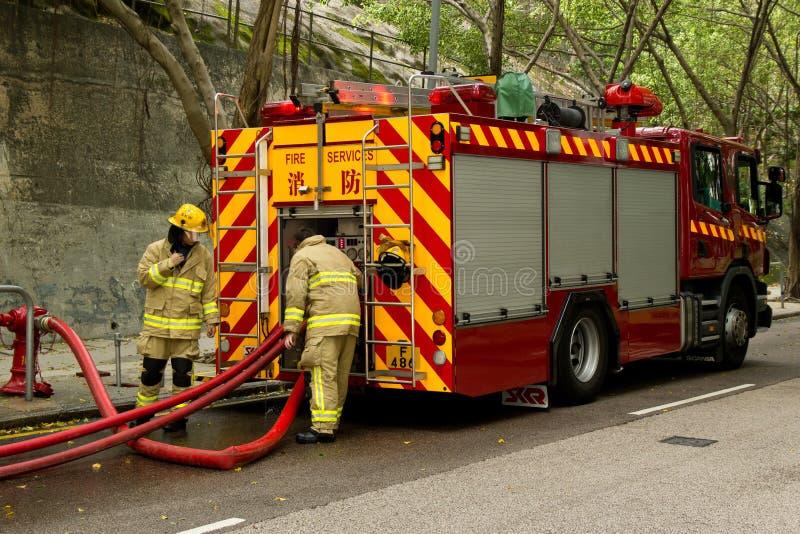 Bomberos y coche de bomberos fotografía de archivo libre de regalías
