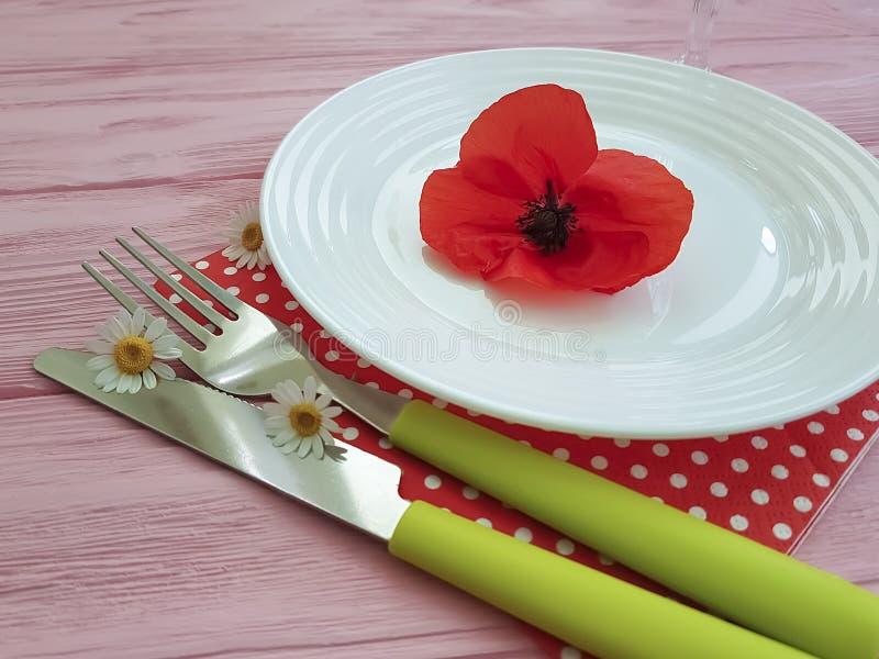 Bombez le restaurant de marguerite de serviette de portion de couteau de fourchette sur un pavot en bois de rouge de fond photo stock