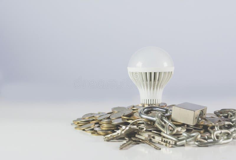 Bombilla ahorro de energía con la cerradura que rodea por las pilas de moneda fotos de archivo libres de regalías