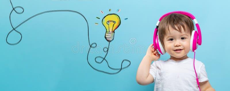 Bombilla con la secuencia con el niño pequeño con los auriculares fotografía de archivo libre de regalías