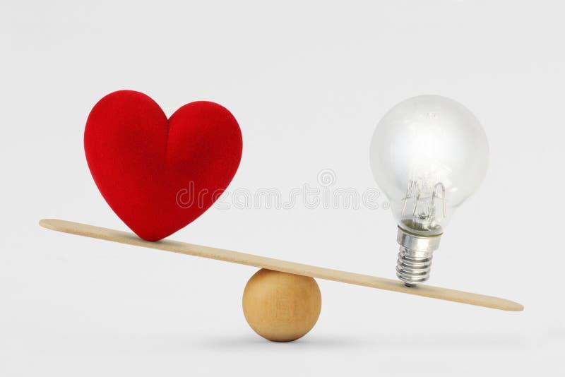 Bombilla del corazón y en la escala - concepto de prioridad del cerebro sobre corazón en vida fotografía de archivo libre de regalías