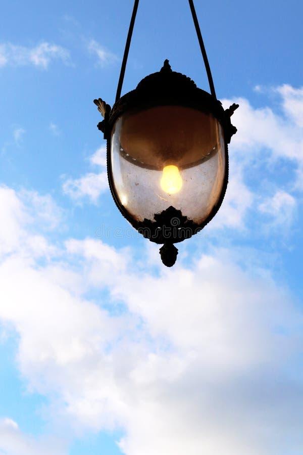 Bombilla del farol del concepto de la gran idea que brilla intensamente en cielo azul imagen de archivo