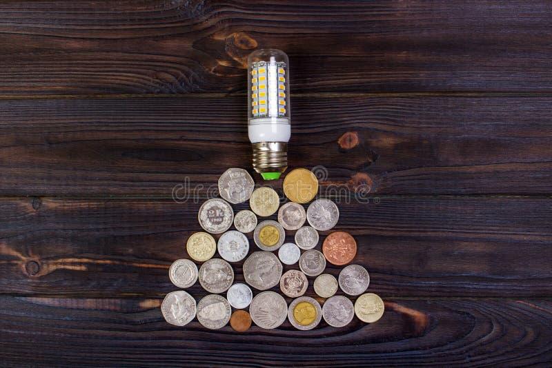 bombilla encendido sobre la pila de monedas - dinero, finanzas, ahorros concepto e idea fotografía de archivo libre de regalías