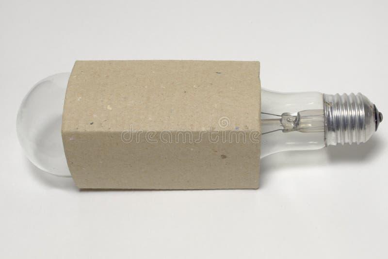 Bombilla incandescente alargada en una caja de cartón foto de archivo