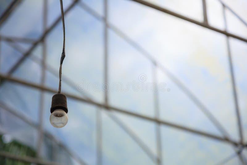 Bombilla incandescente colgante envejecida vieja en el fondo industrial del invernadero de la agricultura equipo de iluminación a imagen de archivo
