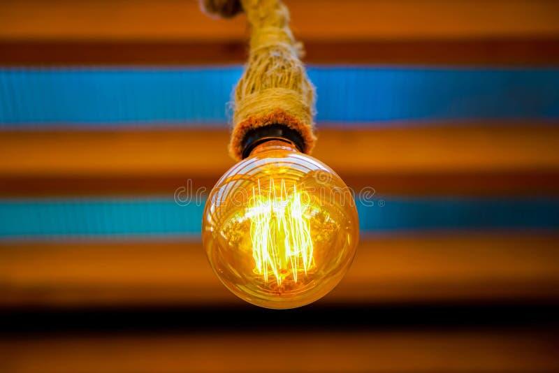 Bombilla que brilla intensamente de oro en un restaurante imagen de archivo