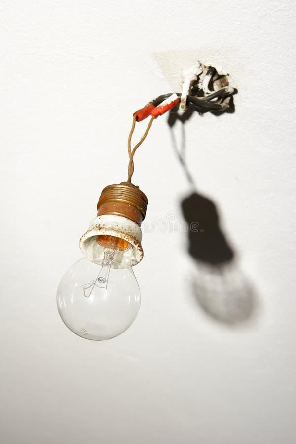 Bombilla que cuelga de los alambres descubiertos fotografía de archivo libre de regalías