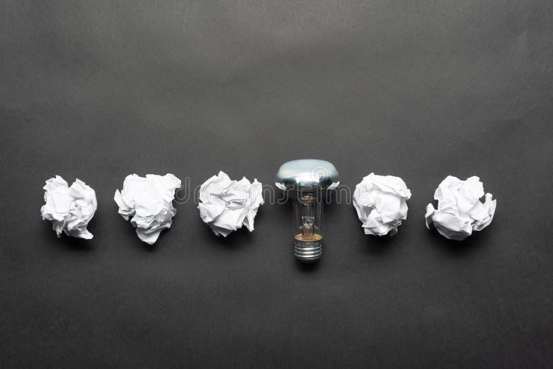 Bombilla y bolas arrugadas del Libro Blanco imagen de archivo libre de regalías